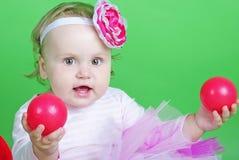 Pequeña muchacha en traje de la rosa en fondo verde Fotografía de archivo libre de regalías