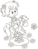 Pequeña muchacha en un oscilación del caballo del juguete en un patio imagen de archivo
