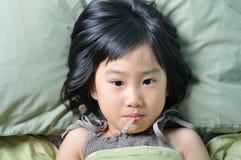 Pequeña muchacha enferma asiática debajo de la manta con temperatura en boca Imagen de archivo libre de regalías