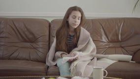 Pequeña muchacha enferma del retrato que sopla su nariz en el sofá, las tabletas y las píldoras en la tabla Concepto de un ni?o e almacen de video