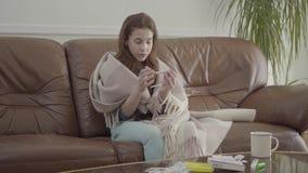 Pequeña muchacha enferma del retrato sentarse en el sofá, las tabletas, las píldoras y la taza en la tabla r Concepto almacen de metraje de vídeo