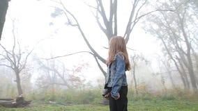Pequeña muchacha europea con un pelo largo, una chaqueta azul, pantalones negros, zapatillas de deporte y ojos azules Un pequeño  almacen de metraje de vídeo