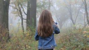 Pequeña muchacha europea con un pelo largo, una chaqueta azul, pantalones negros, zapatillas de deporte y ojos azules Un pequeño  almacen de video