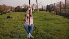 Pequeña muchacha europea en un alambre de la cremallera del patio Cámara lenta El niño femenino feliz monta un oscilación largo d metrajes