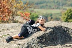 Pequeña muchacha feliz cansada sonriente que miente y que se relaja en los acantilados de piedra Imagen de archivo libre de regalías