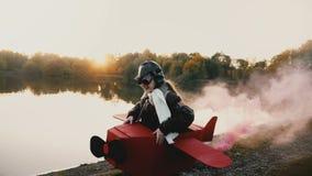 Pequeña muchacha feliz del aviador que juega el funcionamiento en el lago de la puesta del sol en traje plano de la diversión c almacen de metraje de vídeo