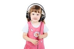 Pequeña muchacha feliz en auriculares grandes Fotografía de archivo libre de regalías