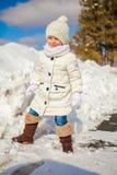 Pequeña muchacha feliz linda que se divierte en la nieve en a imagen de archivo