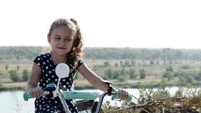 Pequeña muchacha feliz linda que se sienta en una nueva bici en el top de la colina, mirando la cámara y la sonrisa almacen de metraje de vídeo