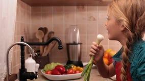 Pequeña muchacha feliz que canta en el fregadero de cocina metrajes