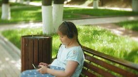Pequeña muchacha gorda con una tableta y los auriculares que se sientan en un banco que escucha la música o que mira un vídeo en  almacen de video