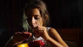 Pequeña muchacha hambrienta un vegetariano que come una granada con avaricia en la noche 4k, a cámara lenta metrajes