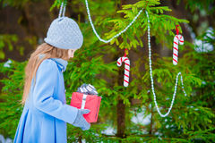 Pequeña muchacha hermosa con el regalo de la caja de la Navidad en día de invierno al aire libre Año Nuevo que viene pronto Imagen de archivo