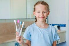 Pequeña muchacha hermosa con los dientes blancos con los cepillos de dientes en manos en el cuarto de baño Fotografía de archivo libre de regalías
