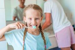 Pequeña muchacha hermosa con los dientes blancos con los cepillos de dientes en manos en el cuarto de baño Foto de archivo