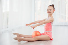 Pequeña muchacha hermosa del gimnasta en el vestido rosado de la ropa de deportes, elemento de la gimnasia del arte interpretativ Fotografía de archivo