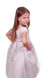 Pequeña muchacha hermosa enojada en una alineada gris. Fotografía de archivo