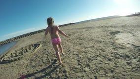 Pequeña muchacha hermosa que corre en la arena almacen de metraje de vídeo