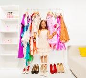 Pequeña muchacha hermosa que elige la ropa en la tienda Fotos de archivo