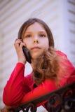 Pequeña muchacha hermosa que habla en el teléfono celular Fotos de archivo libres de regalías