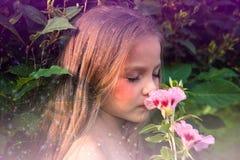 Pequeña muchacha hermosa que huele una flor imagen de archivo