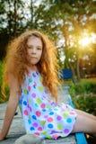 Pequeña muchacha hermosa que se sienta en el puente Foto de archivo libre de regalías