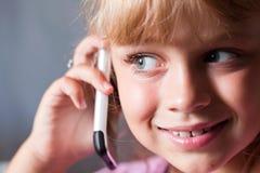 Pequeña muchacha hermosa rubia con el teléfono móvil Fotos de archivo libres de regalías
