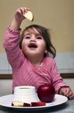 Pequeña muchacha judía que sumerge rebanadas de la manzana en la miel Foto de archivo