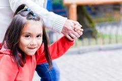 Pequeña muchacha latina feliz y su abuela que llevan a cabo las manos Fotografía de archivo