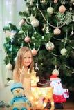 Pequeña muchacha linda cerca del árbol de navidad Niños debajo del árbol de navidad con las cajas de regalo imagen de archivo