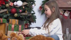 Pequeña muchacha linda con el pelo marrón largo que se sienta cerca del árbol de navidad y de presentes abiertos metrajes