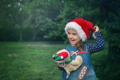 Pequeña muchacha linda con el sombrero de la Navidad y oso de peluche en el jardín Foto de archivo libre de regalías