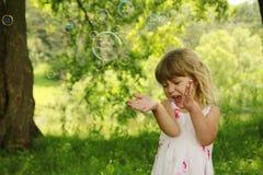 Pequeña muchacha linda con las burbujas de jabón Imágenes de archivo libres de regalías