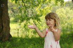 Pequeña muchacha linda con las burbujas de jabón Imagen de archivo