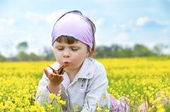 Pequeña muchacha linda con una mariposa. imagenes de archivo