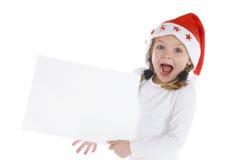 Pequeña muchacha linda de la Navidad con una muestra en blanco Imágenes de archivo libres de regalías