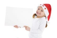 Pequeña muchacha linda de la Navidad con una muestra en blanco Fotografía de archivo
