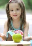Pequeña muchacha linda del niño con Apple Fotos de archivo