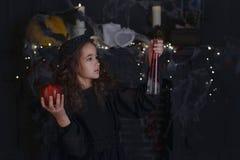 Pequeña muchacha linda del niño de la bruja en el traje y las decoraciones de Halloween Fotos de archivo