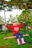 Pequeña muchacha linda del trastorno que balancea en el oscilación de madera al aire libre Foto de archivo