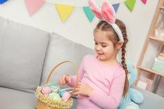 Pequeña muchacha linda en el concepto de la celebración de pascua de los oídos del conejito en casa que mira la cesta con los hue imagen de archivo libre de regalías