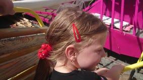 Pequeña muchacha linda en la atracción del funfair Carrusel del Funfair Ciérrese para arriba de la muchacha feliz hermosa que tie almacen de metraje de vídeo