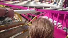 Pequeña muchacha linda en la atracción del funfair Carrusel del Funfair Muchacha feliz alegre que grita durante paseo del carruse almacen de metraje de vídeo