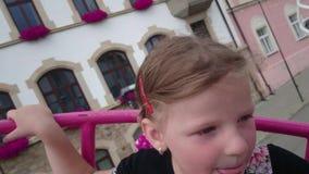 Pequeña muchacha linda en la atracción del funfair Carrusel del Funfair Muchacha feliz alegre que grita durante paseo del carruse metrajes