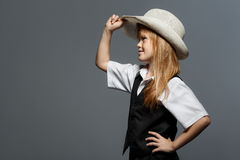 Pequeña muchacha linda en sombrero, en la camisa blanca, en el chaleco negro, mirando al lado aislado sobre gris Imagenes de archivo