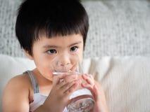 Pequeña muchacha linda feliz que sostiene un vidrio y que bebe el agua C imagen de archivo
