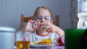 Pequeña muchacha linda hermosa que come un huevo hervido en la tabla en la cocina almacen de video