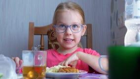Pequeña muchacha linda hermosa que come un huevo hervido en la tabla en la cocina almacen de metraje de vídeo