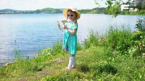 Pequeña muchacha linda que come el helado en la forma de corazón cerca del mar metrajes