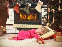 Pequeña muchacha linda que duerme debajo del árbol de navidad para S que espera Fotos de archivo libres de regalías